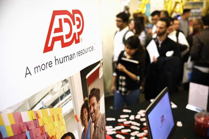 Premium EA: ADP LLC signage is displayed as job seekers wait in line during the TechFair LA job fair in Los Angeles, California