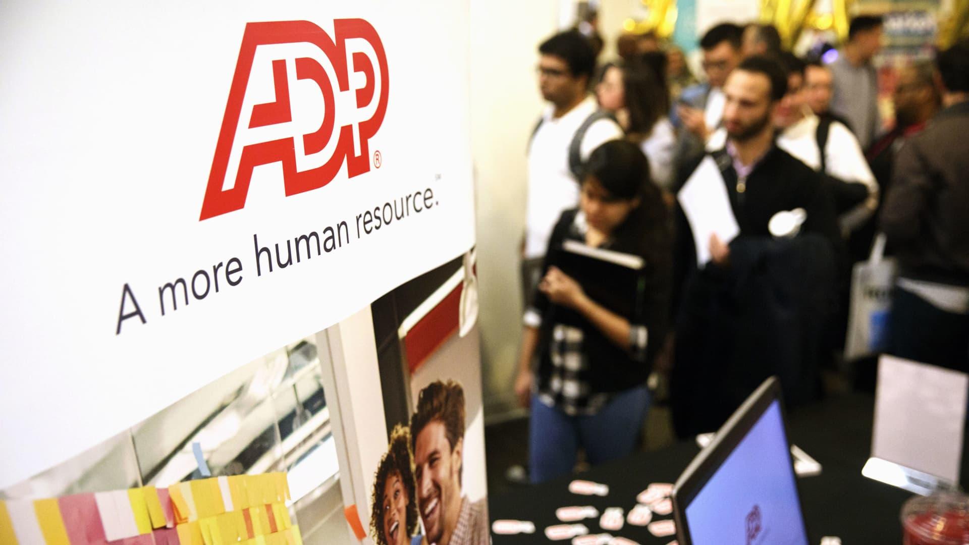 ADP LLC signage is displayed as job seekers wait in line during the TechFair LA job fair in Los Angeles, California.