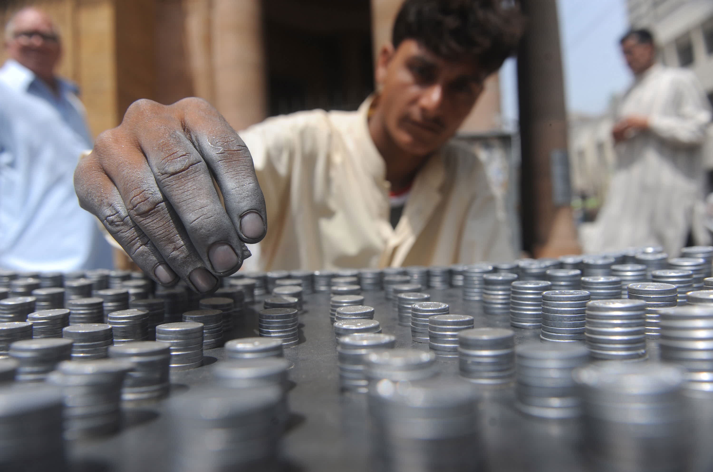 A Pakistani vendor arranges coins at his roadside stall in Karachi.
