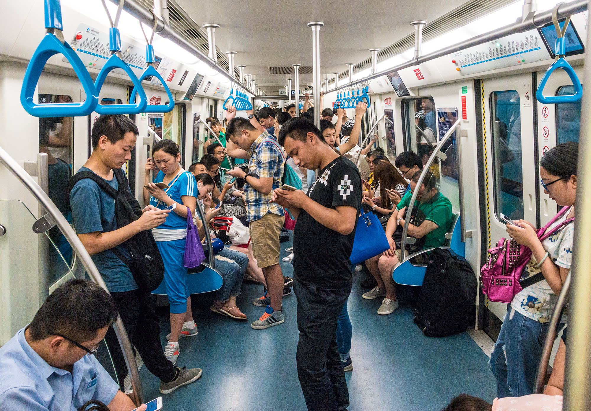 Passengers look at smartphones on a subway train on April 6, 2017 in Chengdu, China.