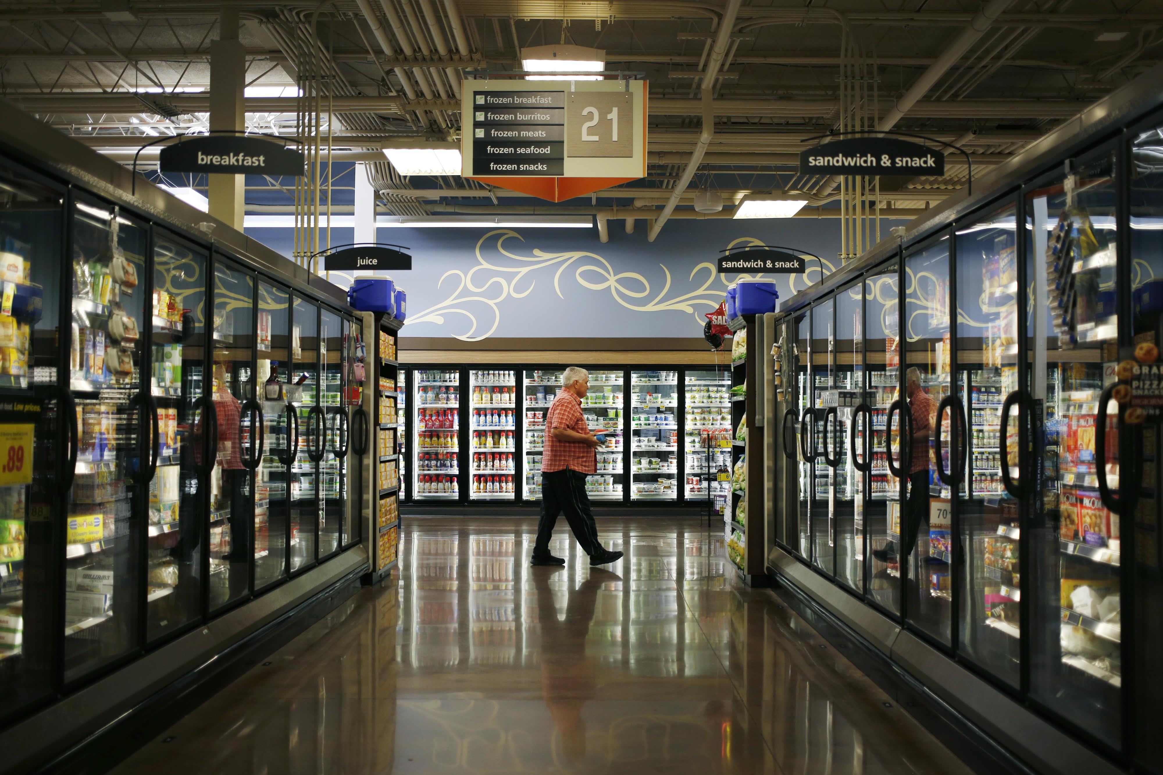 A customer walks past the frozen food aisle inside a Kroger Co. grocery store in Louisville, Kentucky.