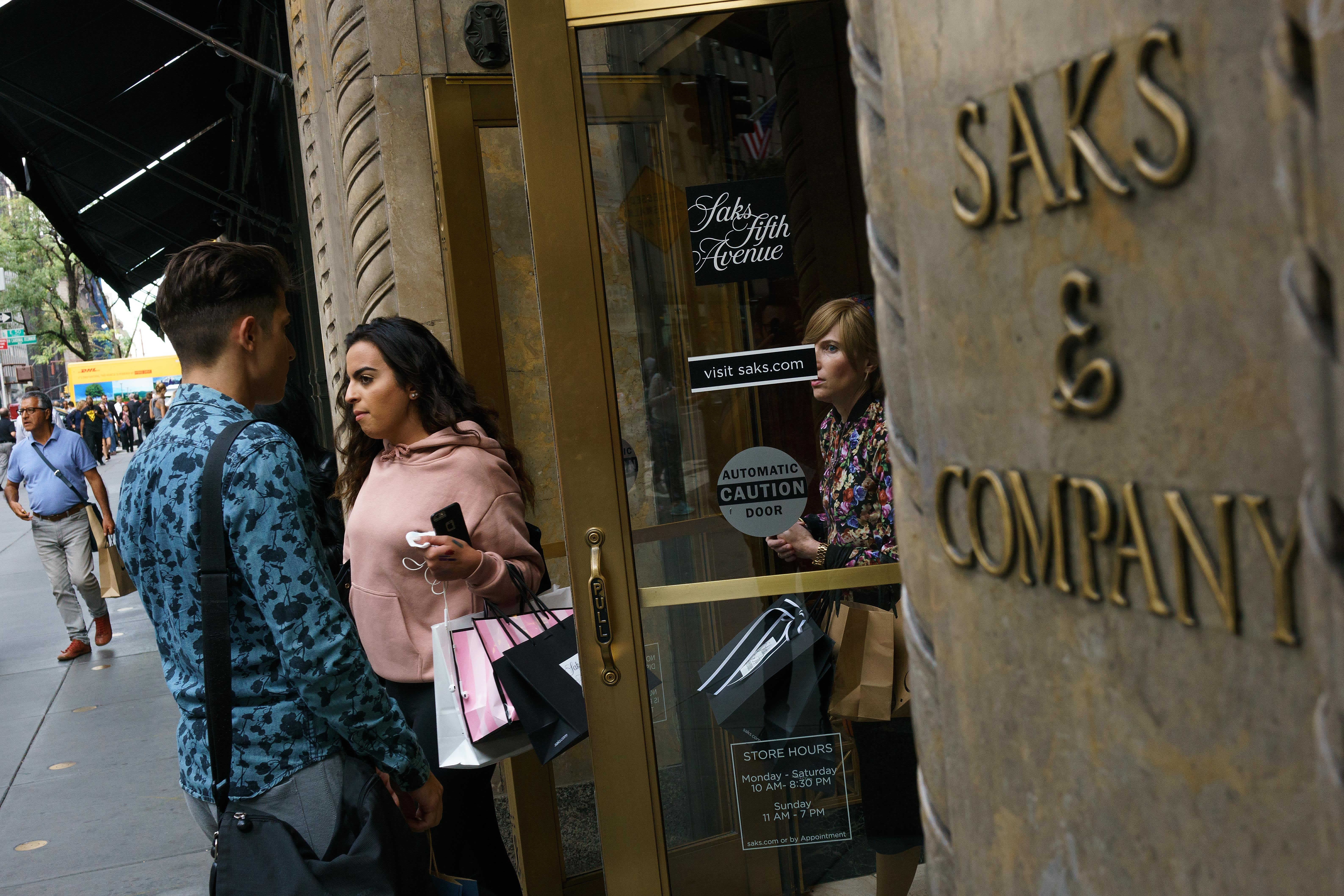 Shoppers exit and enter a Saks Fifth Avenue store on Fifth Avenue in New York City.