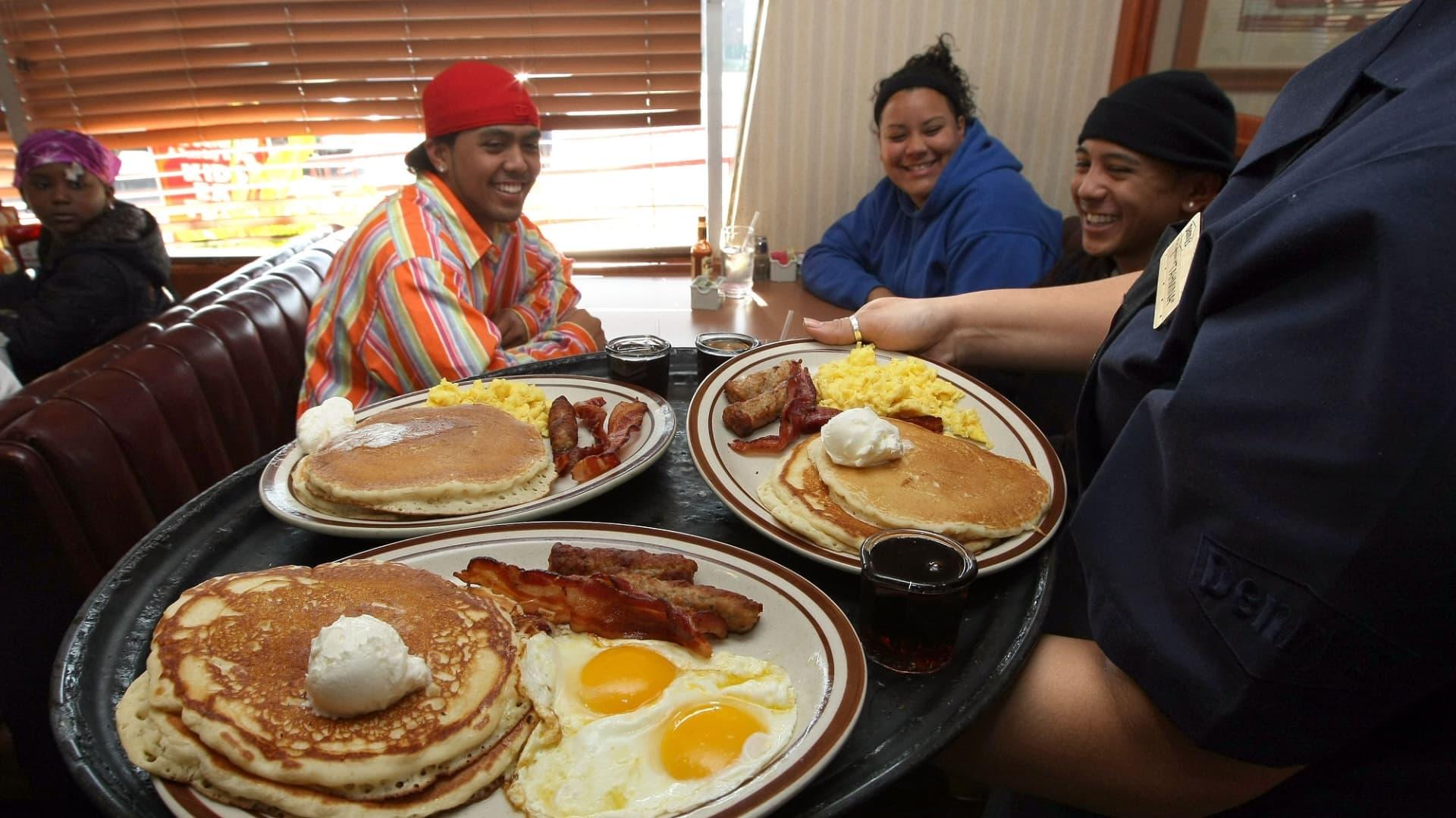 Denny's waitress serves breakfast to customers.