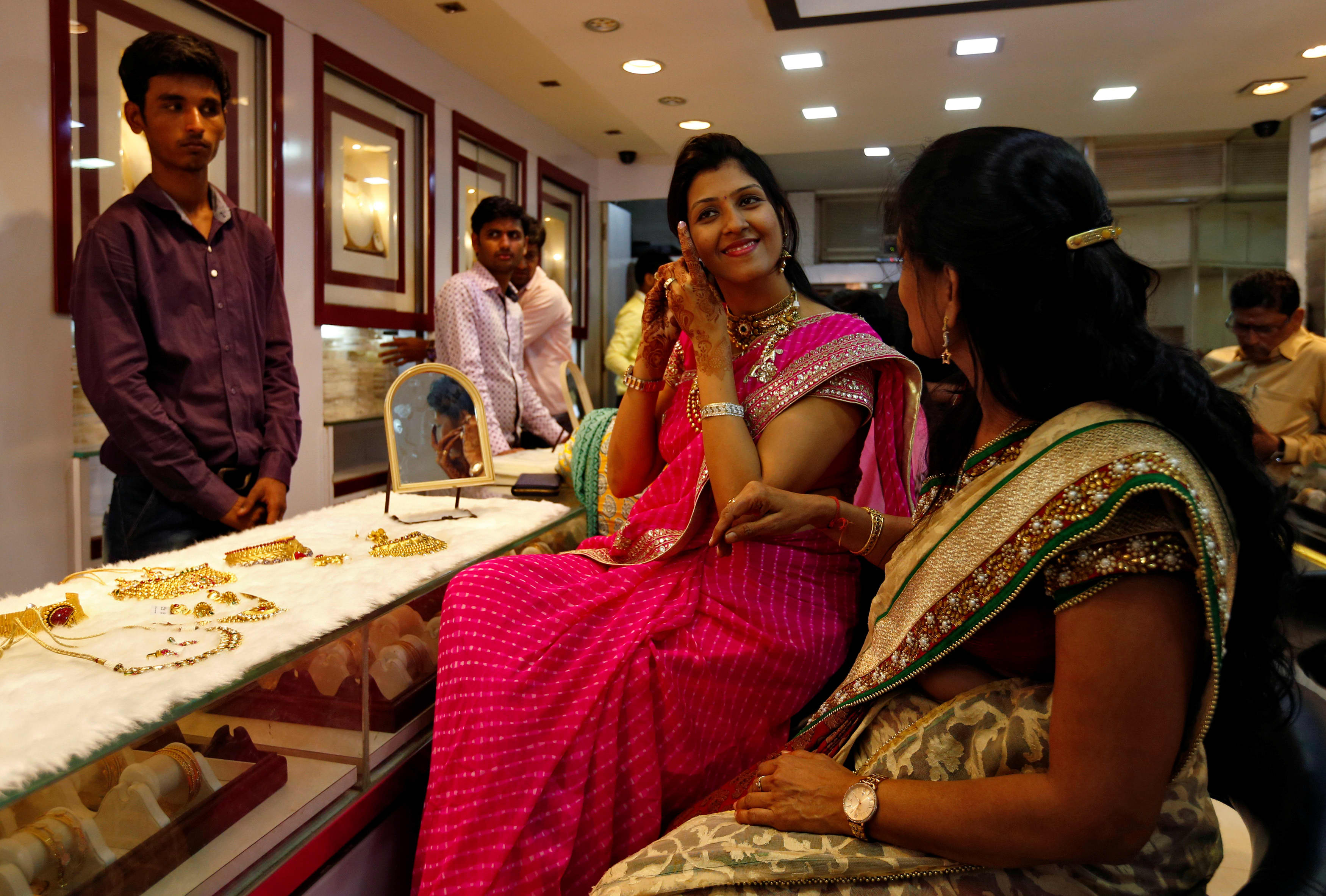 A woman tries a gold earring at a jewellery showroom in Mumbai, India on October 28, 2016.