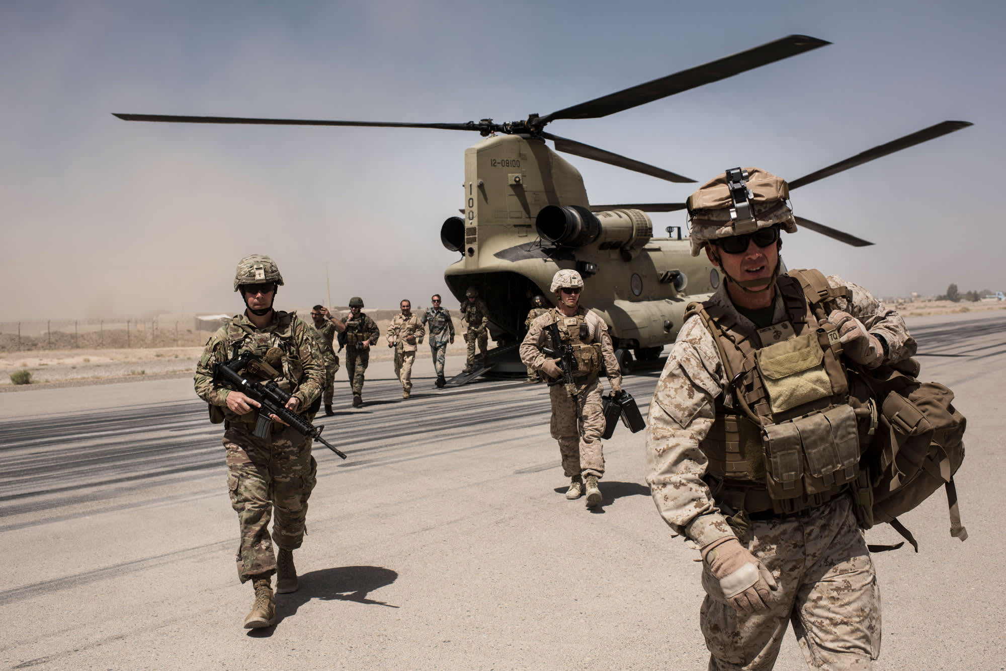 U.S. service members walk off a helicopter on the runway at Camp Bost in Helmand Province, Afghanistan.