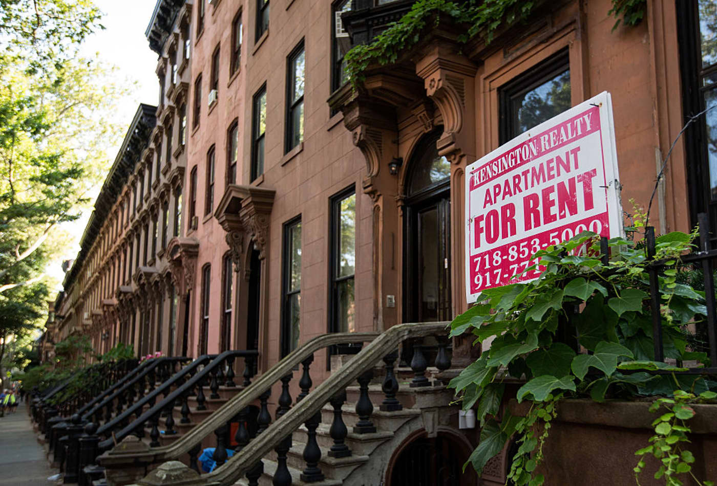 A Sign Advertises An Apartment For Rent Along Row Of Brownstone Townhouses In Brooklyn New York