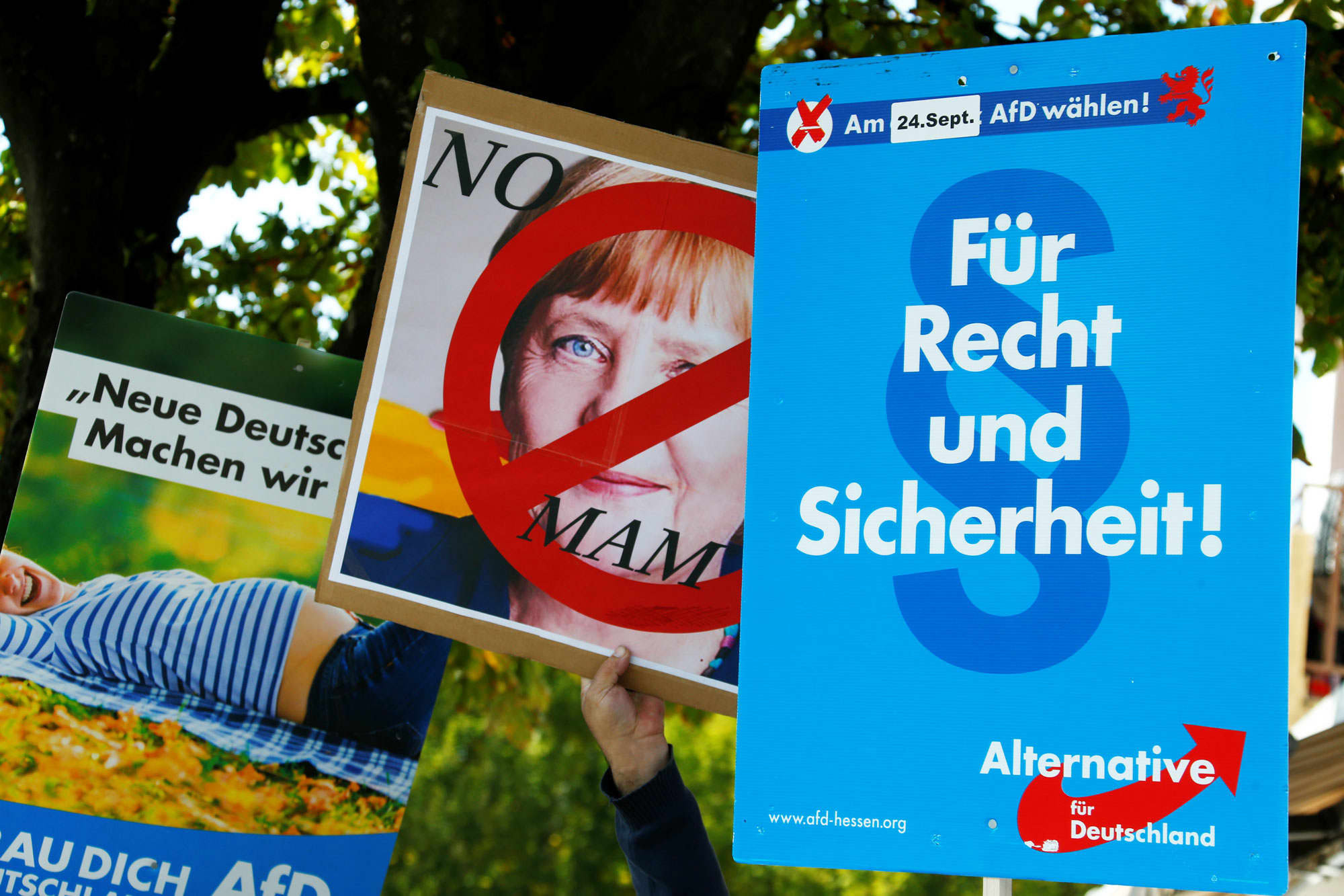 People hold anti-immigration party Alternative fuer Deutschland AfD placards as they protest against German Chancellor Angela Merkel campaigning in Heppenheim, Germany, September 22, 2017.