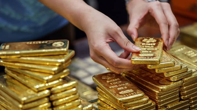 An employee arranges gold bars for a photograph at the YLG Bullion International headquarters in Bangkok, Thailand.
