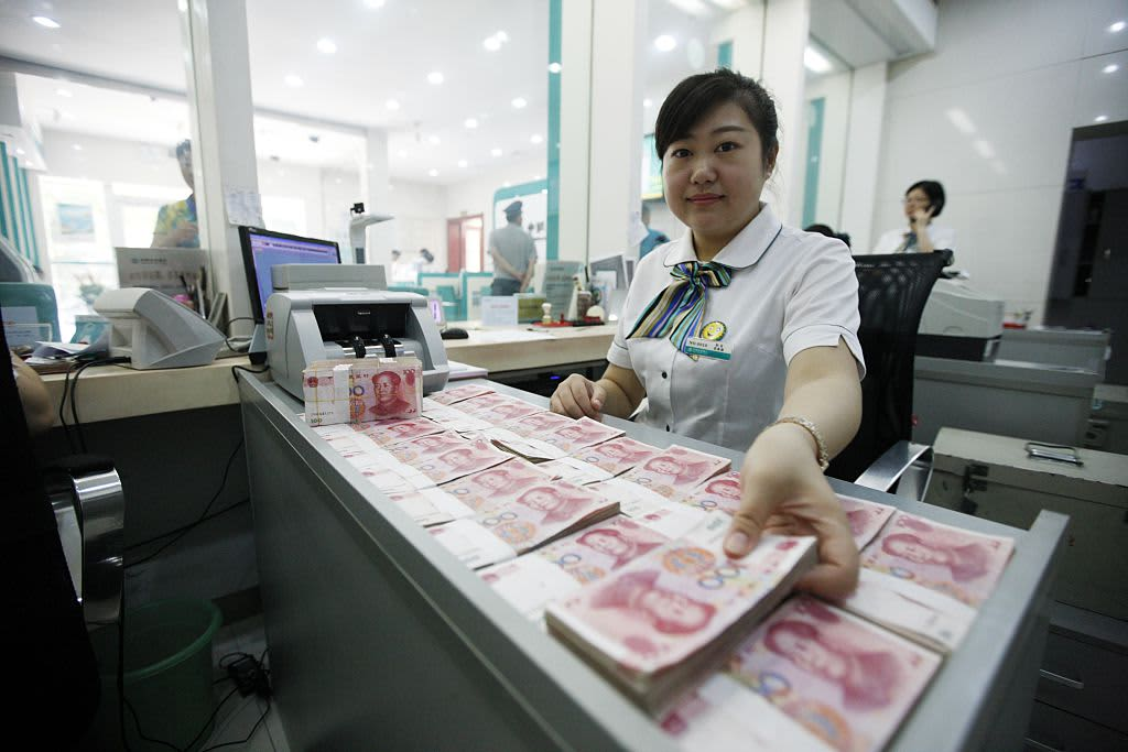 A worker counts Chinese currency Renminbi at a bank in China.