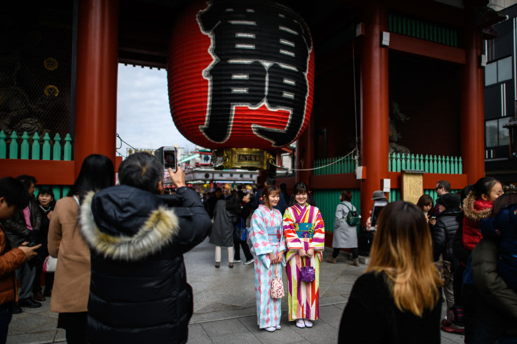 Tourists in kimonos have their photograph taken next to a huge lantern in Senso-ji buddhist temple, on January 19, 2018, in Tokyo.