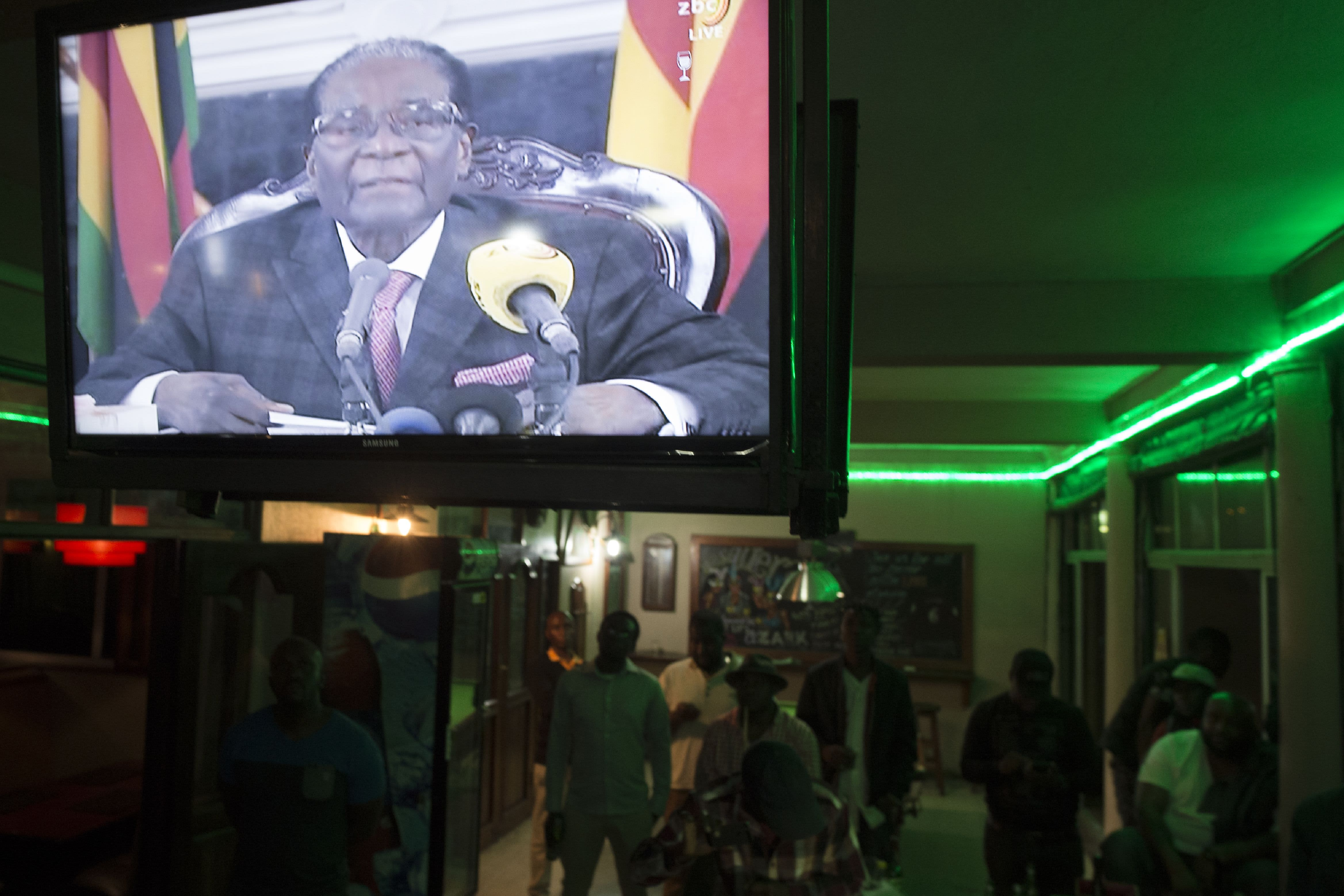 Zimbabweans watch a television address by then President Robert Mugabe in Harare on November 19, 2017.