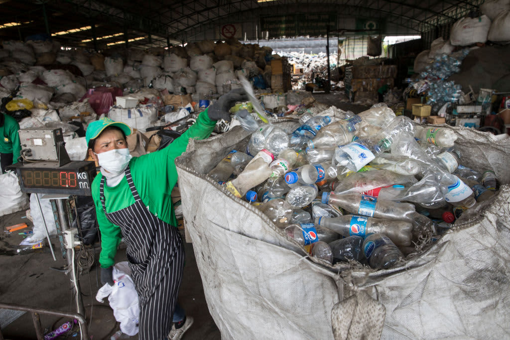 A worker manually separates waste at the Wongpanit Suvarnabhumi recycle collection center on