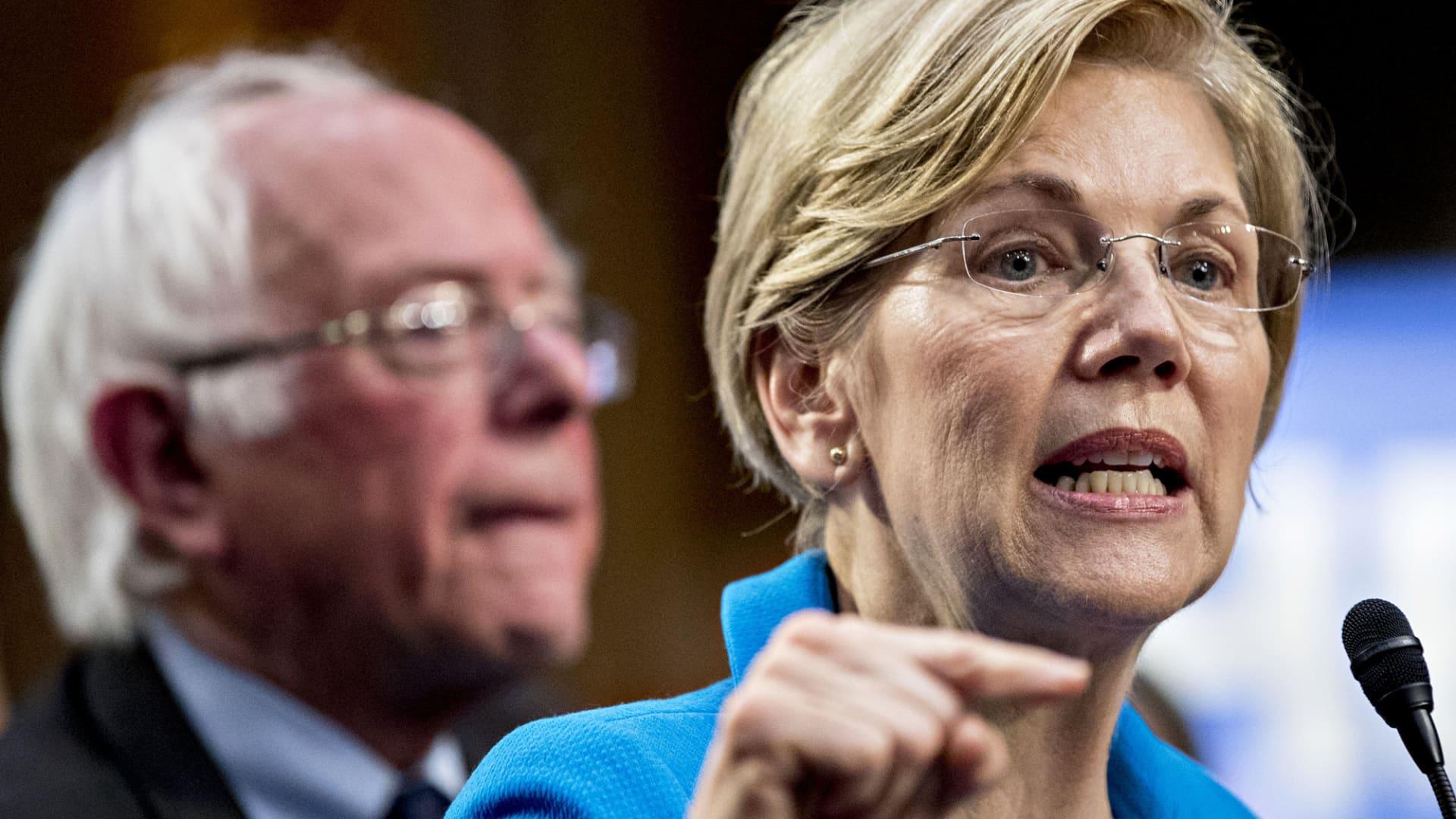 Senator Elizabeth Warren speaks as Senator Bernie Sanders looks on.