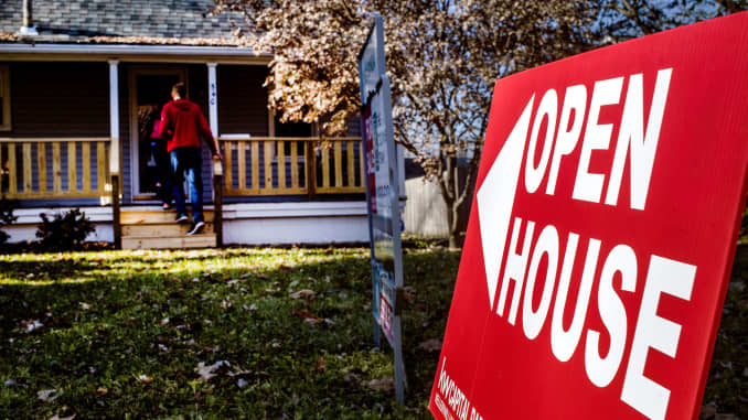 An 'Open House' sign is displayed as potential home buyers arrive at a property for sale in Columbus, Ohio.