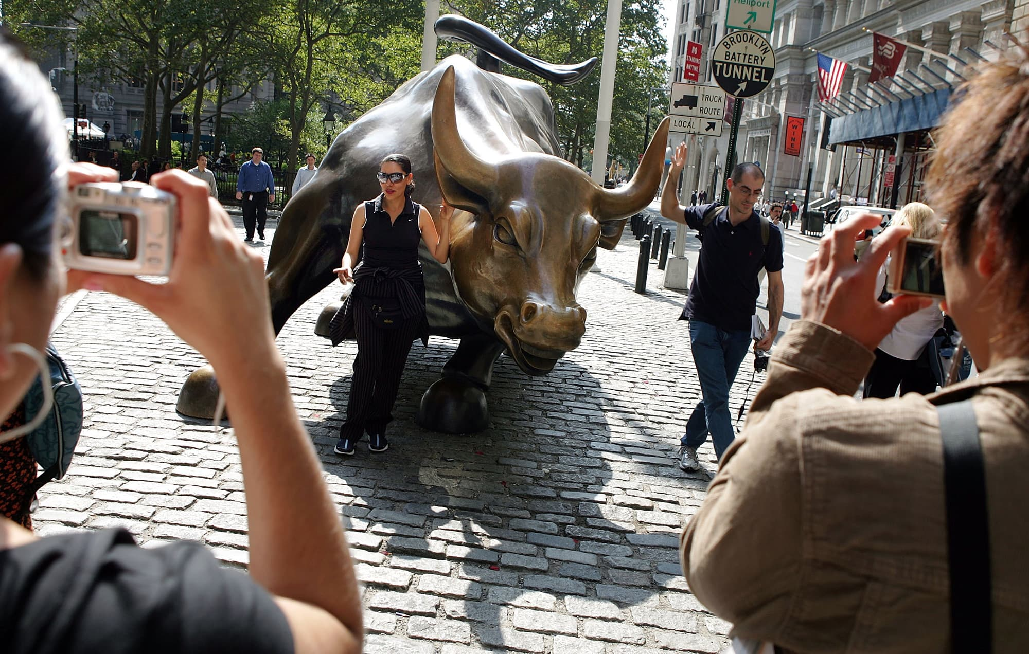 People take photos of the famous bull statue near the New York Stock Exchange in New York City.