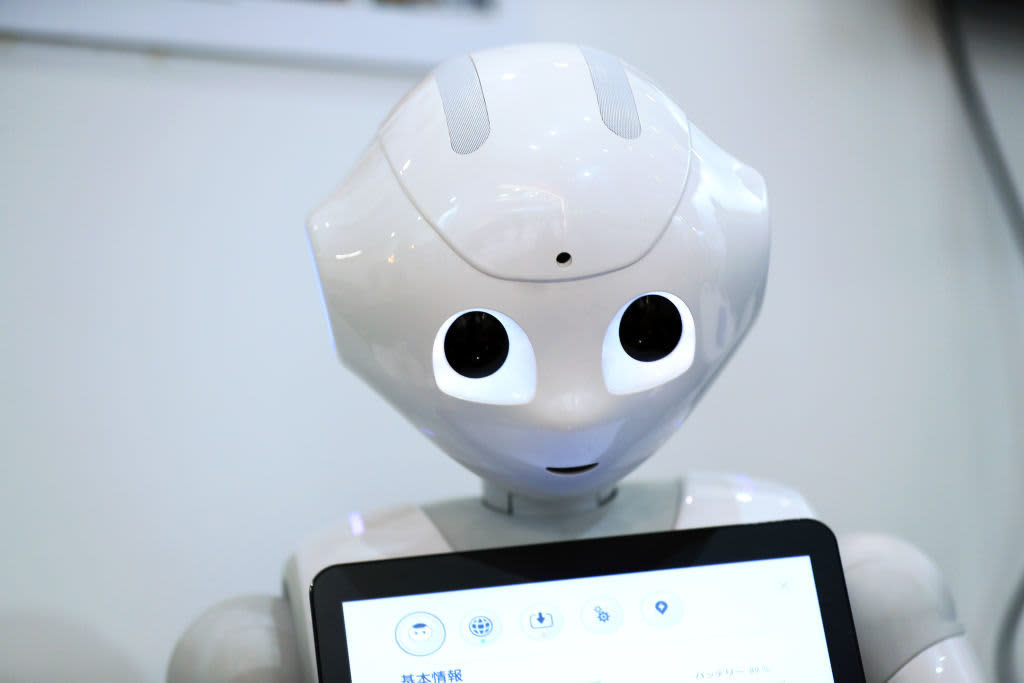 Pepper, the humanoid robot, holds a tablet device at a tech fair.