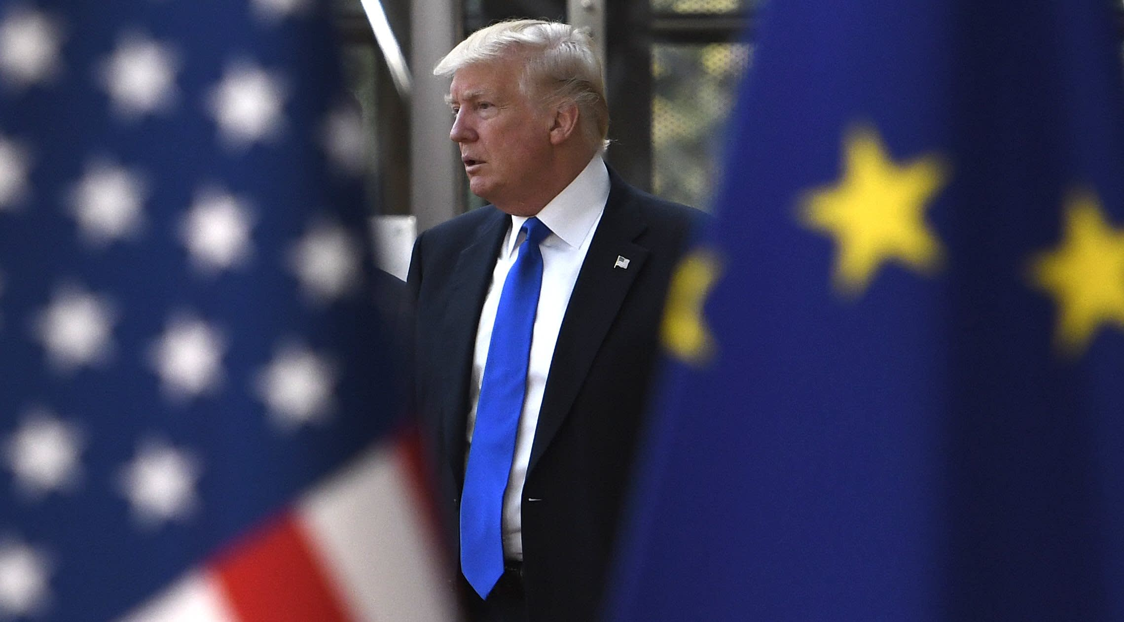American President Donald Trump seen in between the flags of the U.S. and the European Union,