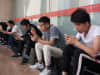 People use their mobile phones outside an office building in Beijing on May 24, 2018.
