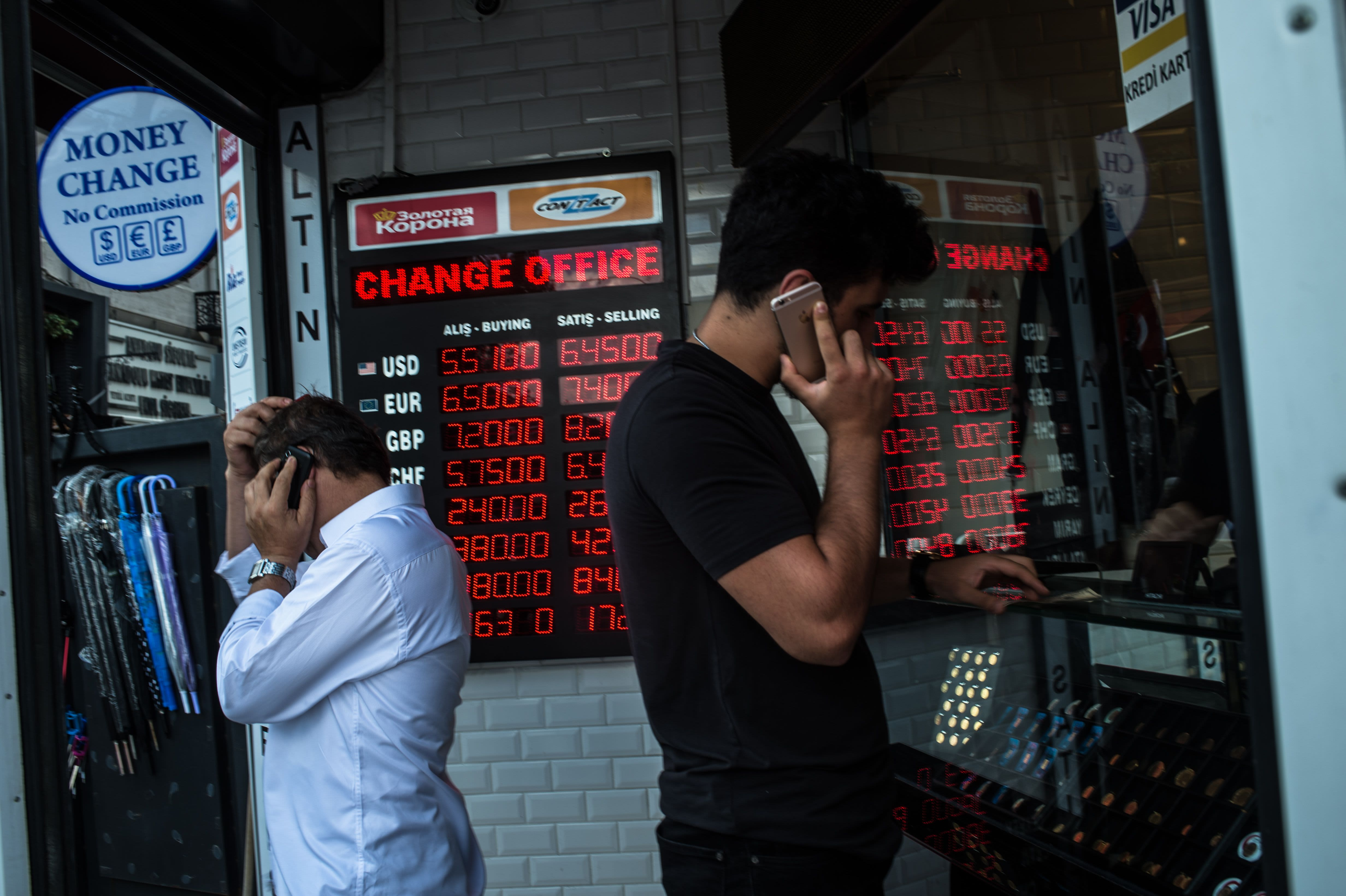 People check currency exchange rates at a currency exchange office on August 11, 2018 in Istanbul.