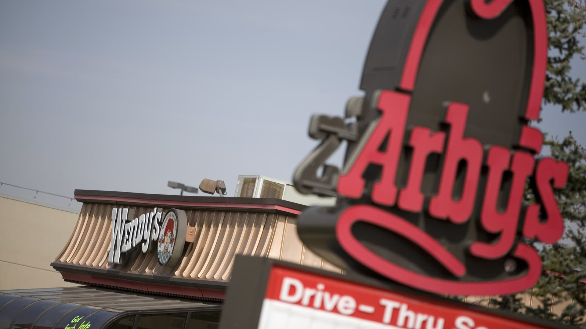 An Arby's restaurant sign stands near a Wendy's restaurant in Lakewood, Colorado