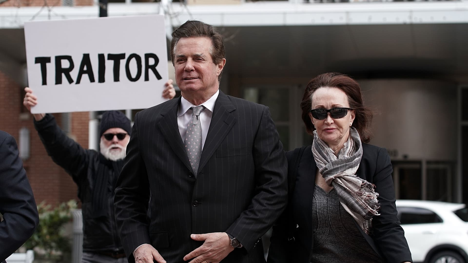 Former Trump campaign manager Paul Manafort (2nd R) arrives with his wife Kathleen Manafort (R) at the Albert V. Bryan U.S. Courthouse for an arraignment hearing as a protester holds up a sign March 8, 2018 in Alexandria, Virginia.