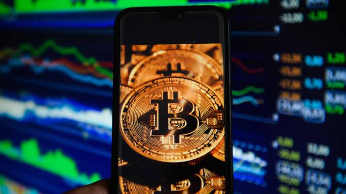 A bitcoin logo on a mobile phone.