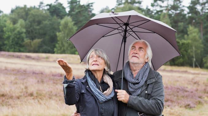 GP: Senior couple under umbrella, retirement, seeking safety