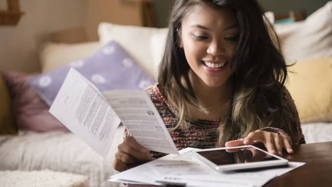 Mixed Race woman paying bills using digital tablet