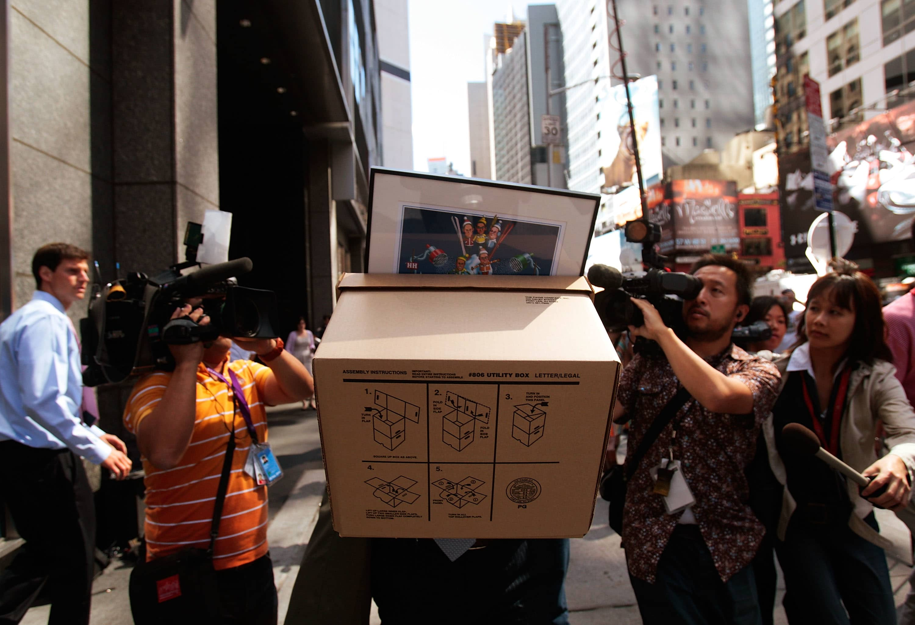 An employee of Lehman Brothers Holdings Inc. carries a box out of the company's headquarters as he is followed by the media September 15, 2008 in New York City.