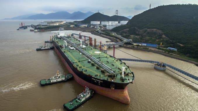 An oil tanker sits beside transfer pipes at a terminal as it prepares to unload its cargo of fuel on July 4, 2018 in Zhoushan, China.