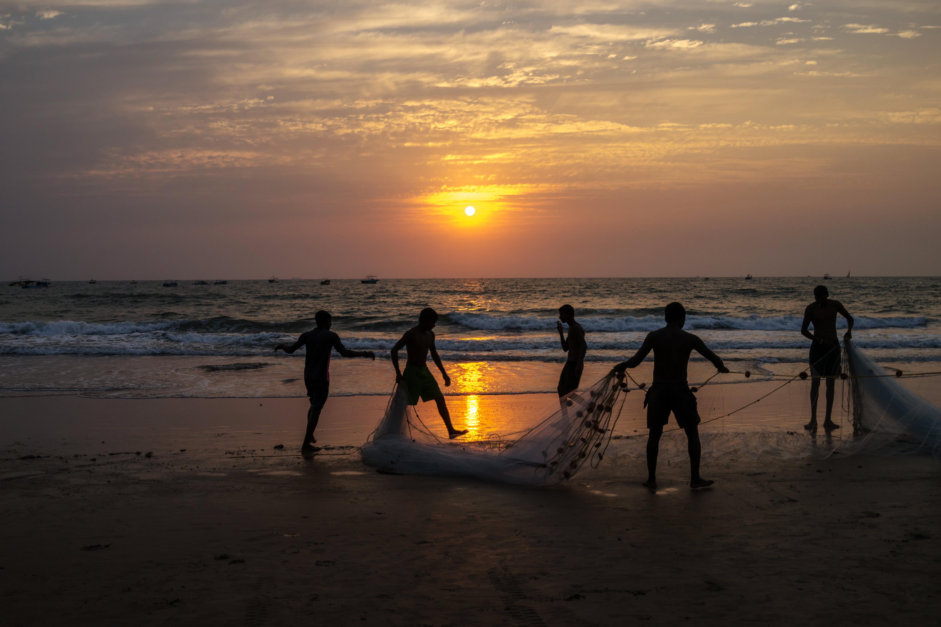 Local fisherman pack a fishing net as the sun sets on Baga beach in Bardez, Goa, India, on Mar. 9, 2016.