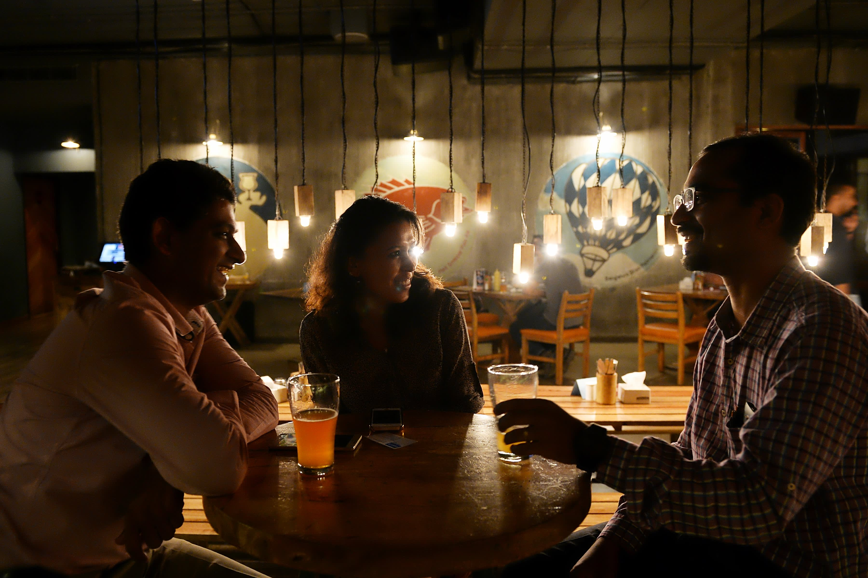 Customers share a conversation over beer at The Arbour Microbrewery in Bangalore.