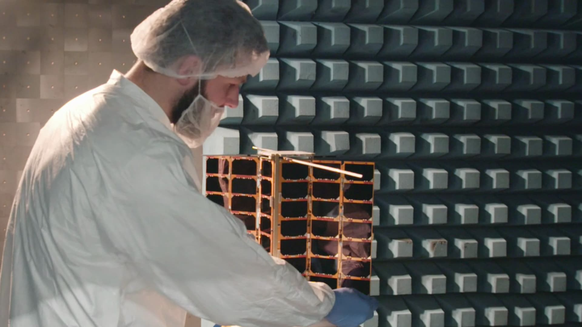 A Spire Global engineer works on a satellite in a testing chamber.