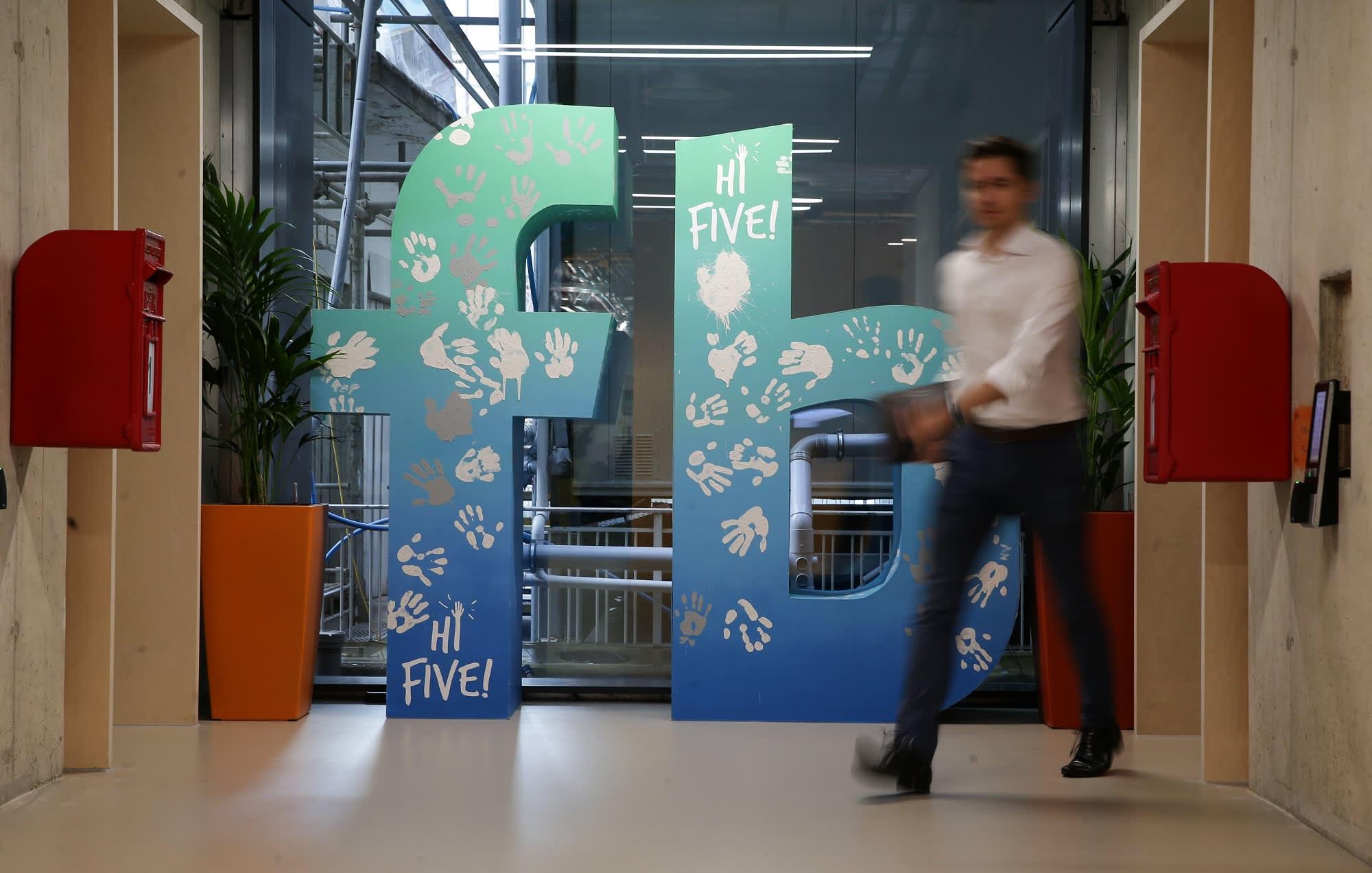 GP:employee walks past a Facebook logo