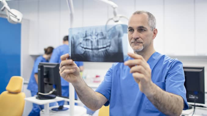 GP: dentist orthodontist holding X-ray image