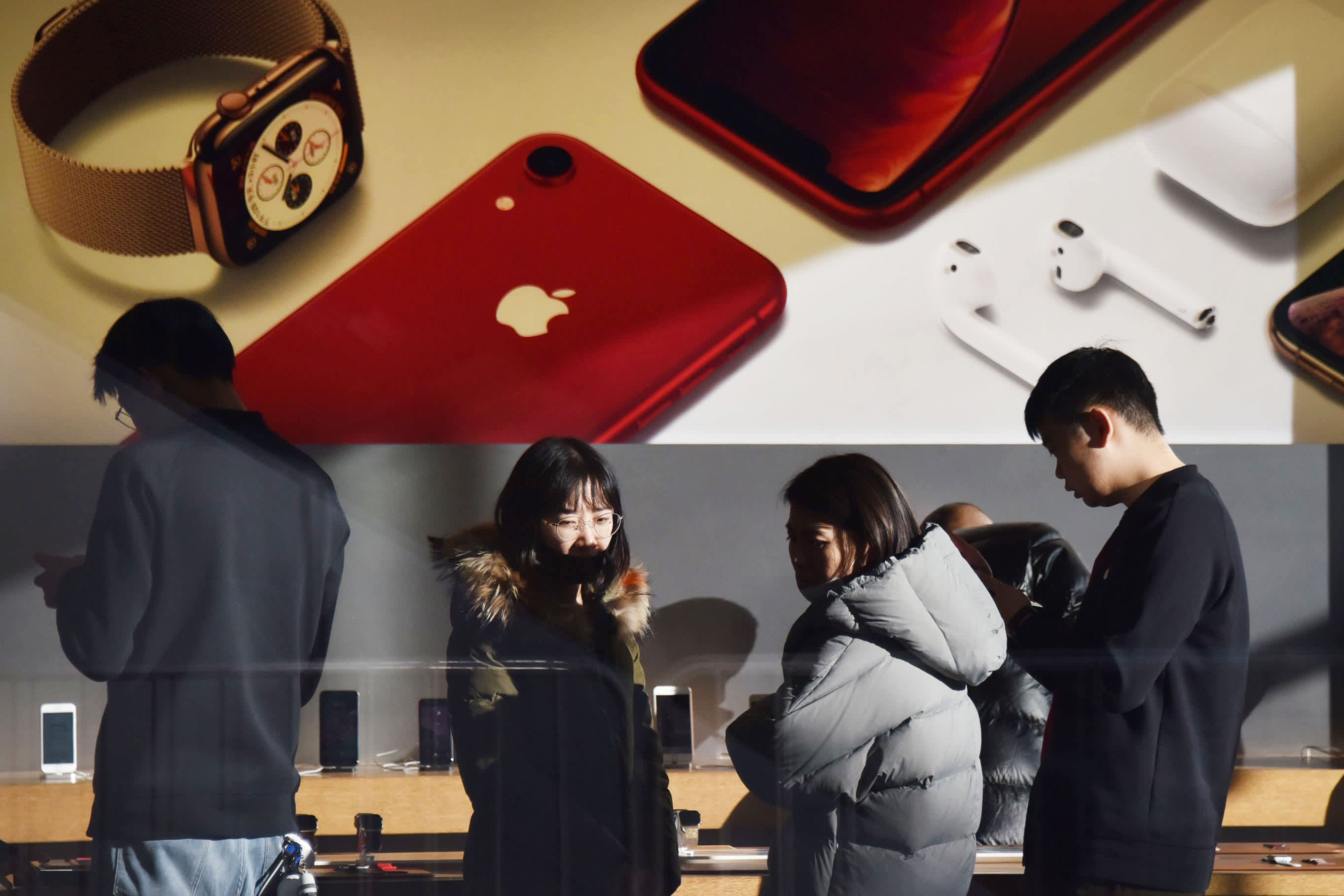 Customers look at products in an Apple store in Beijing on December 11, 2018.