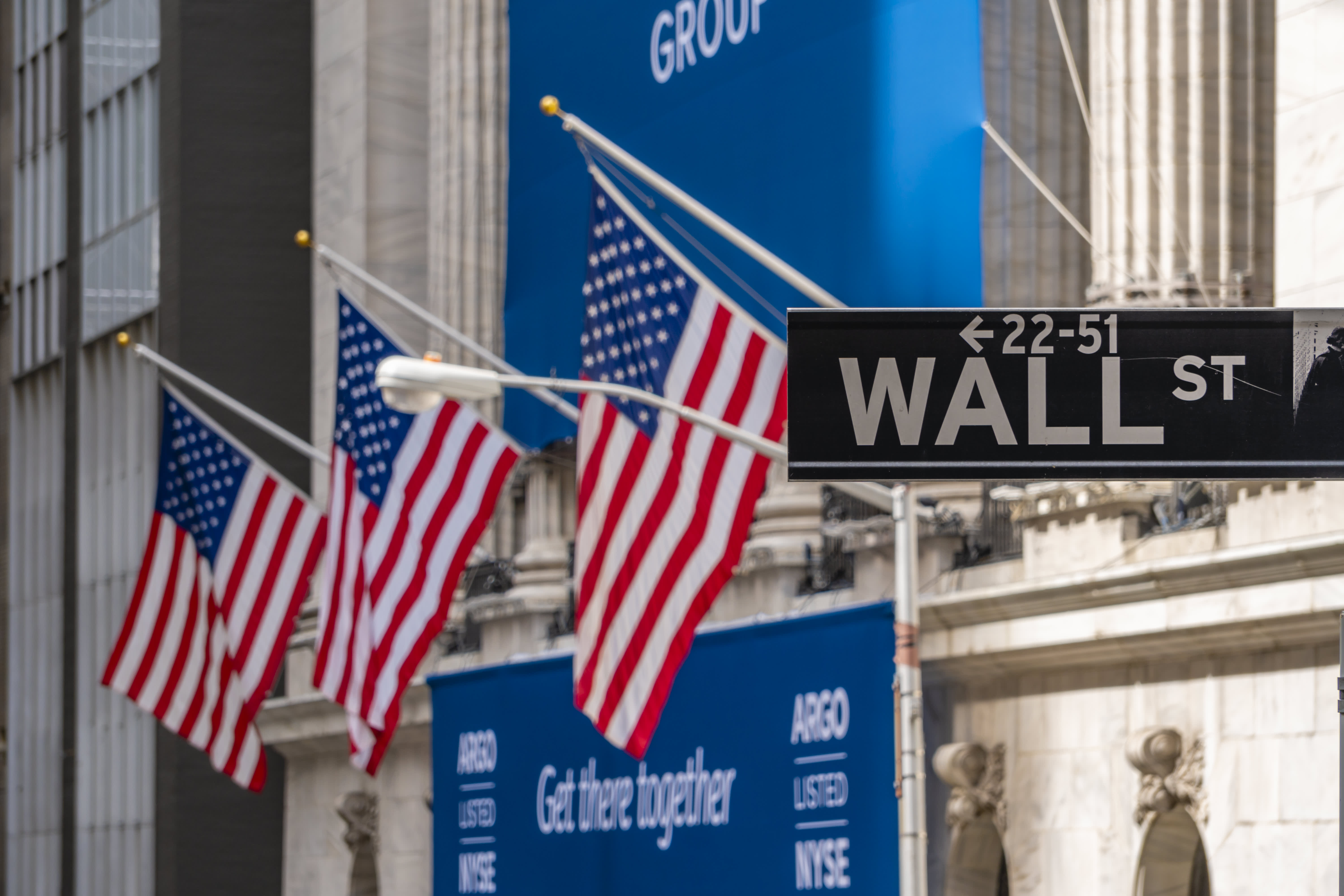 New York, USA - May 8, 2018: Wall Street sign near New York Stock Exchange with flags of the United States. It is the world's most significant financial center.