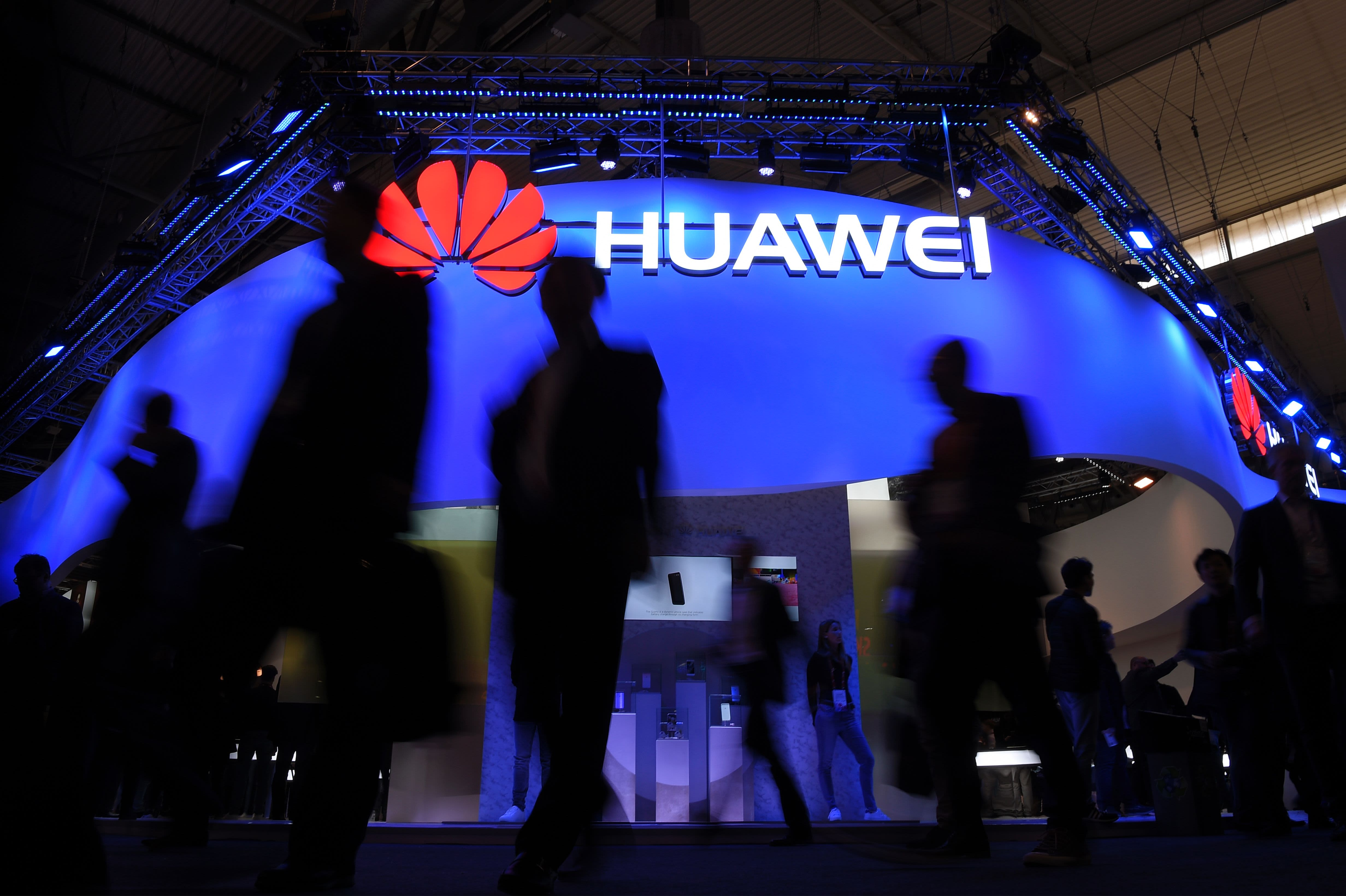 Visitors pass in front of the Huawei's stand on the first day of the Mobile World Congress in Barcelonaon on February 27, 2017 in Barcelona.