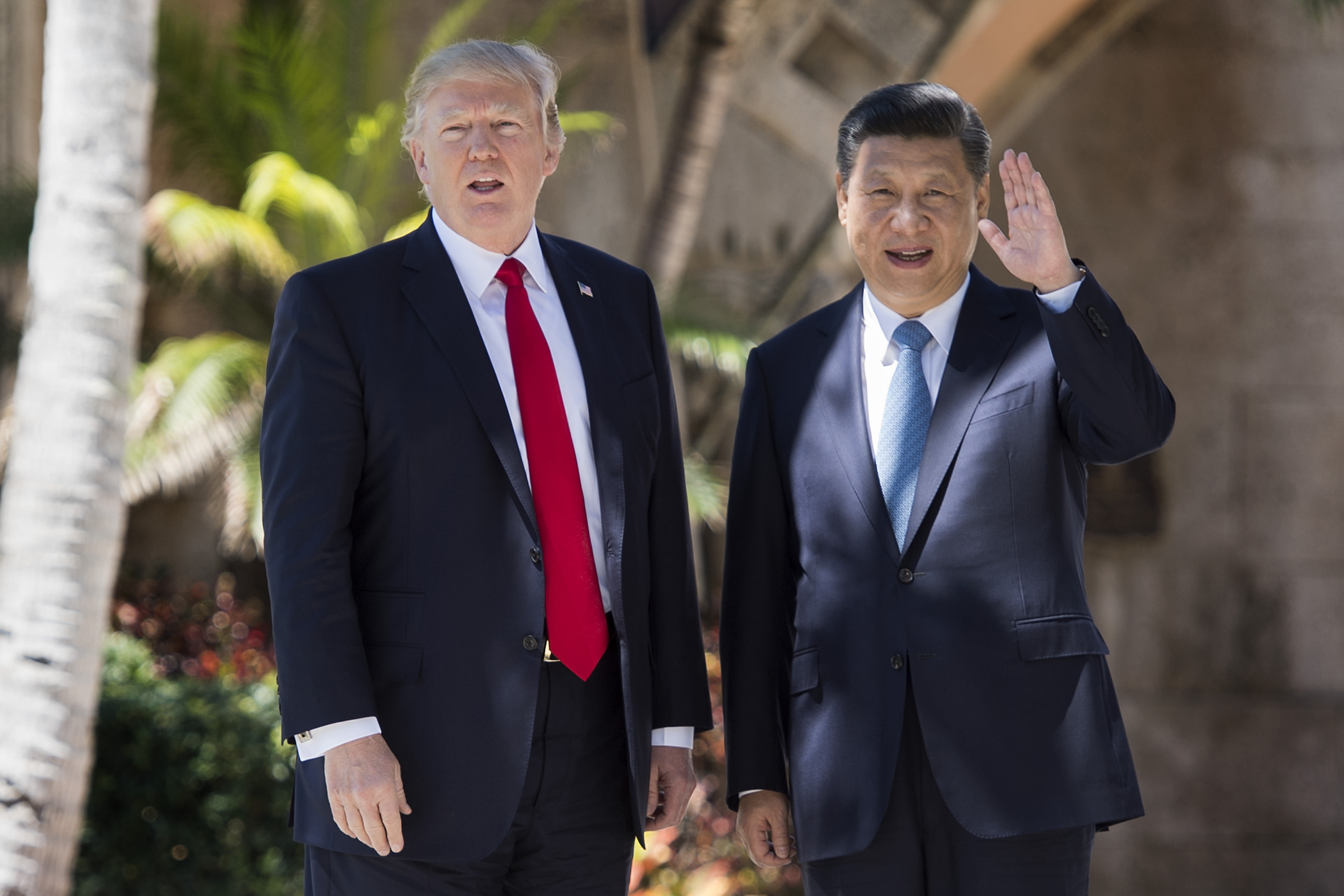 Chinese President Xi Jinping (R) waves to the press as he walks with US President Donald Trump at the Mar-a-Lago estate in West Palm Beach, Florida, April 7, 2017.