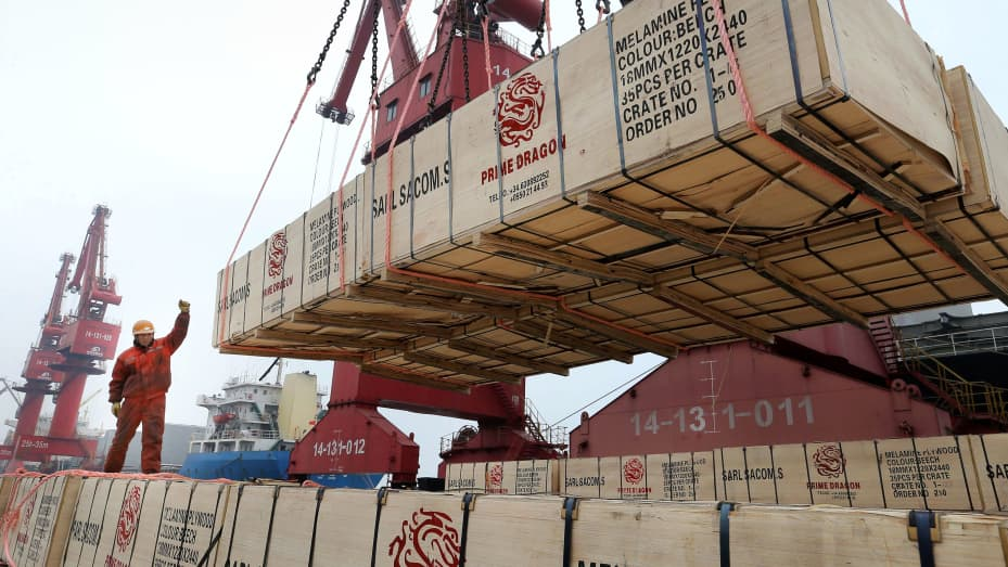 A worker gestures as a crane lifts goods for export onto a cargo vessel at a port in Lianyungang, China, February 13, 2019.