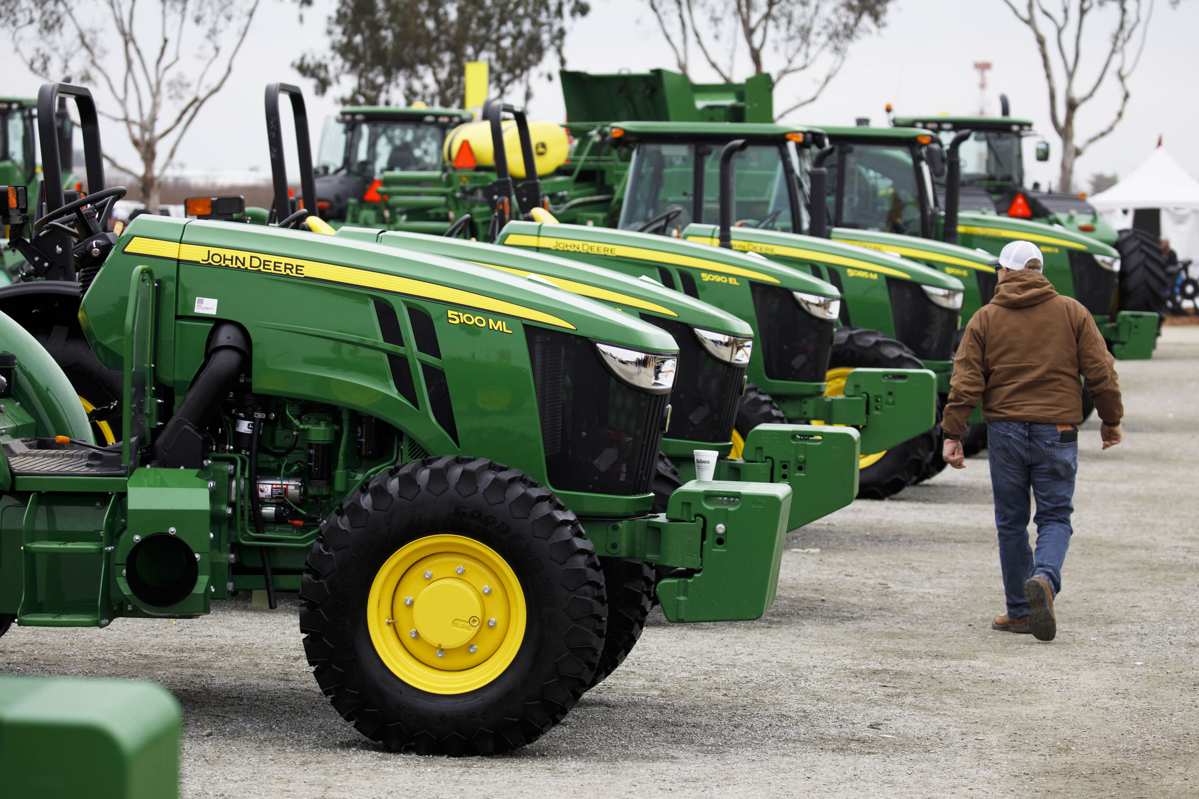 An attendee passes in front of John Deere brand tractors displayed during the World Agriculture Expo in Tulare, California, on Tuesday, Feb. 12, 2019.