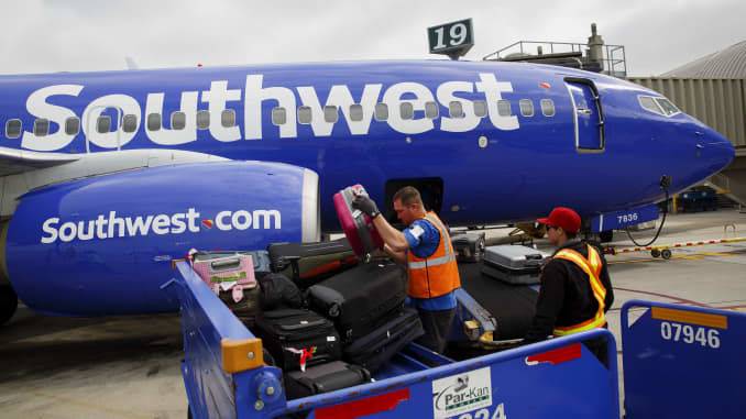Ground operations employees load baggage onto a Southwest Airlines Boeing 737 aircraft on the tarmac at John Wayne Airport (SNA) in Santa Ana, California.