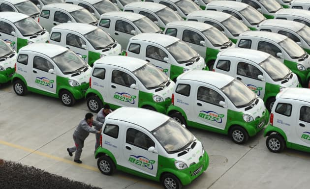 AP: Chinese workers push an EV past electric vehicles displayed at a parking lot of Zhejiang Kandi Vehicles Co