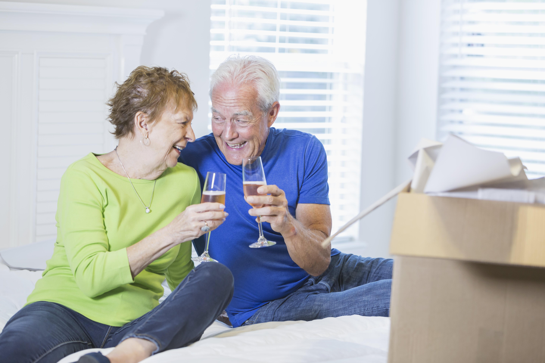 Senior couple celebrating move with champagne