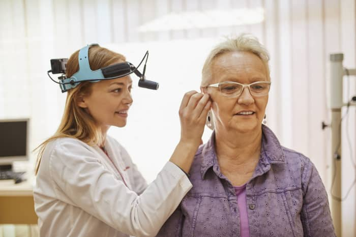 GP: audiologist ENT physician examining ear of a senior woman