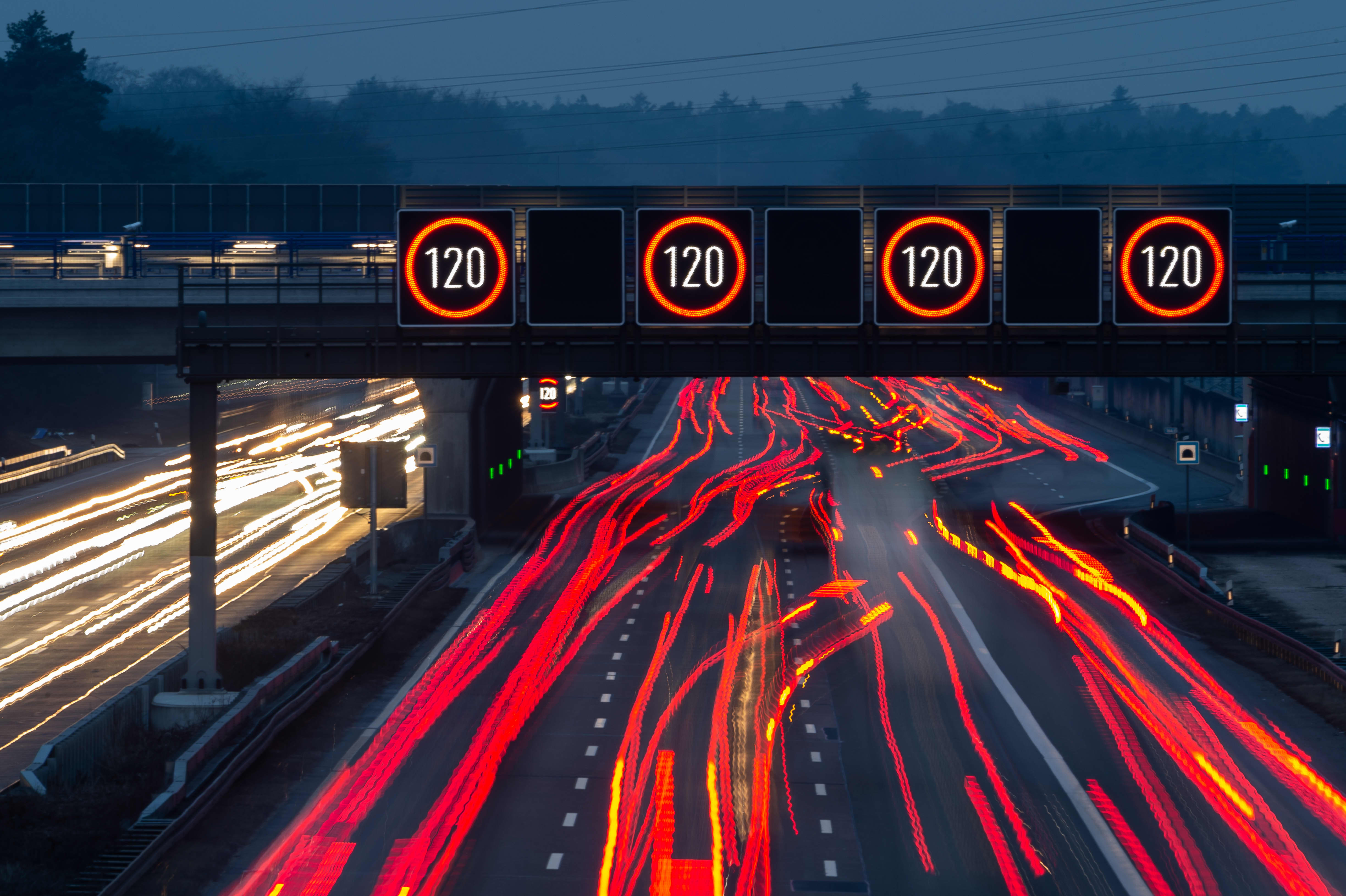 Illuminated panels indicate a speed limit of 120 kilometers per hour above the A3 motorway near Frankfurt Airport, Germany.