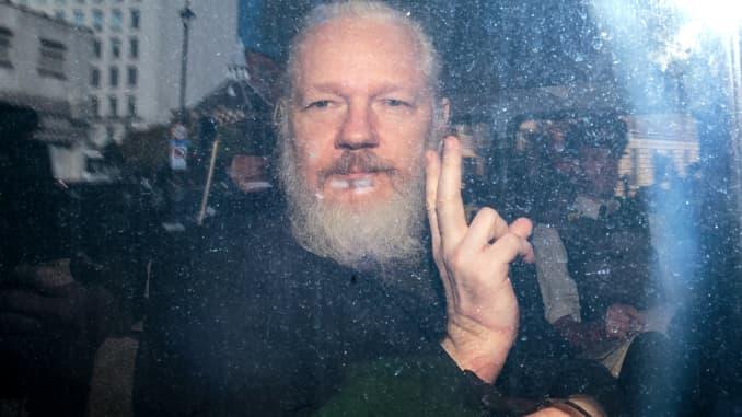 Julian Assange ra hiệu với giới truyền thông từ một chiếc xe cảnh sát khi anh ta đến tòa án Westminster Magistrates vào ngày 11 tháng 4 năm 2019 ở London, Anh.