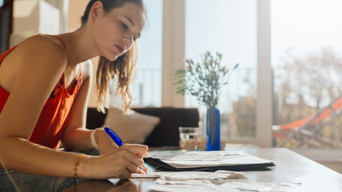 Woman doing bookkeeping at home, receipts, taxes, small business