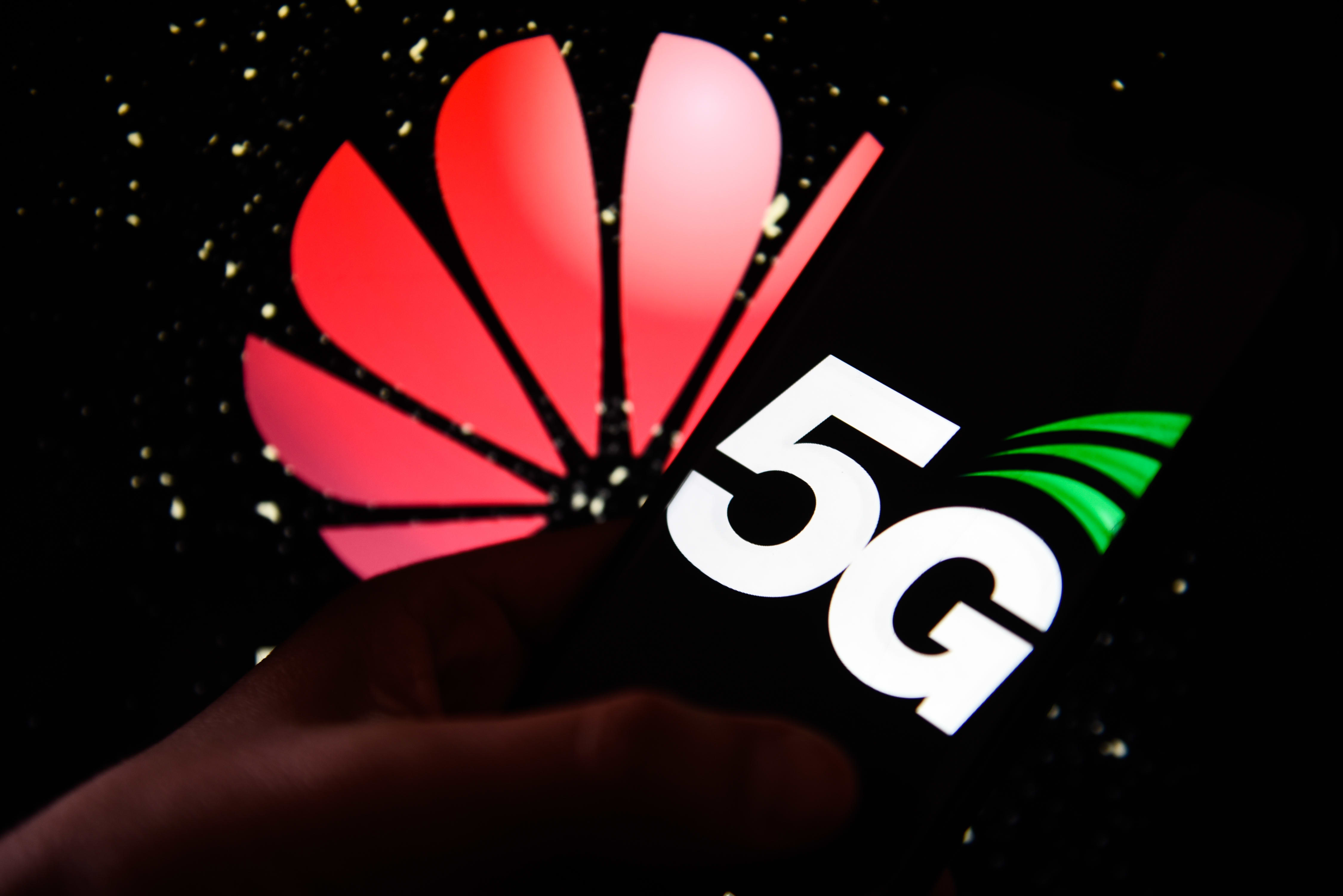 5G logo is seen on an android mobile phone with Huawei logo on the background.