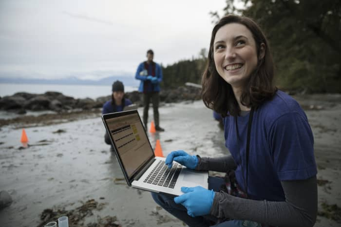GP: eco-friendly female scientist with laptop on beach